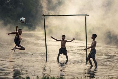 Kinder beim Fußballspiel auf knöchelhoch überschwemmtem Platz