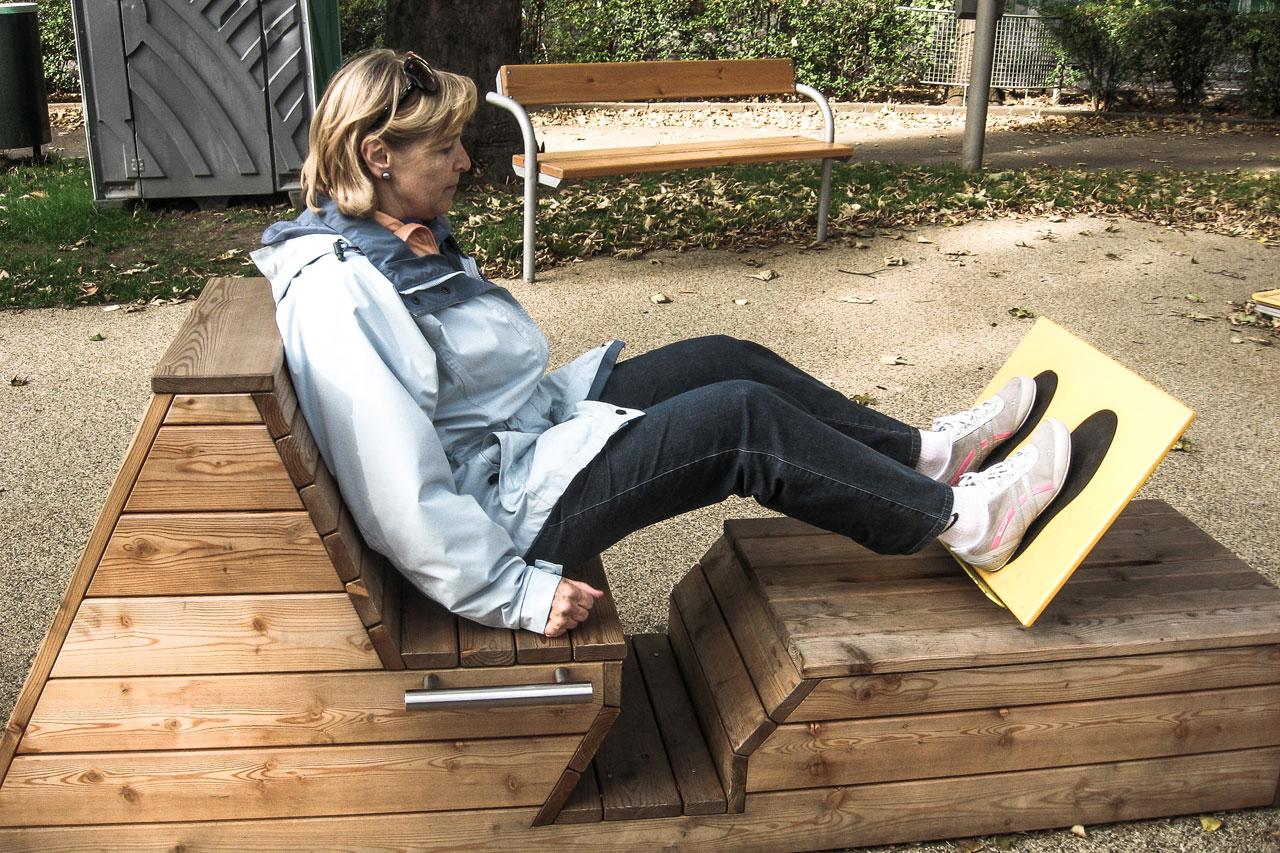 Pensionistin trainiert ihre Oberschenkel-Muskulatur auf einer Outdoor-Beinpresse