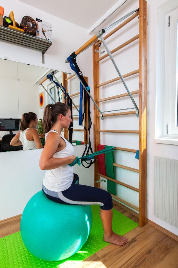 Trainerin Bernadette Hörner trainiert den mittleren Rücken mit Theraband an der Sprossenwand
