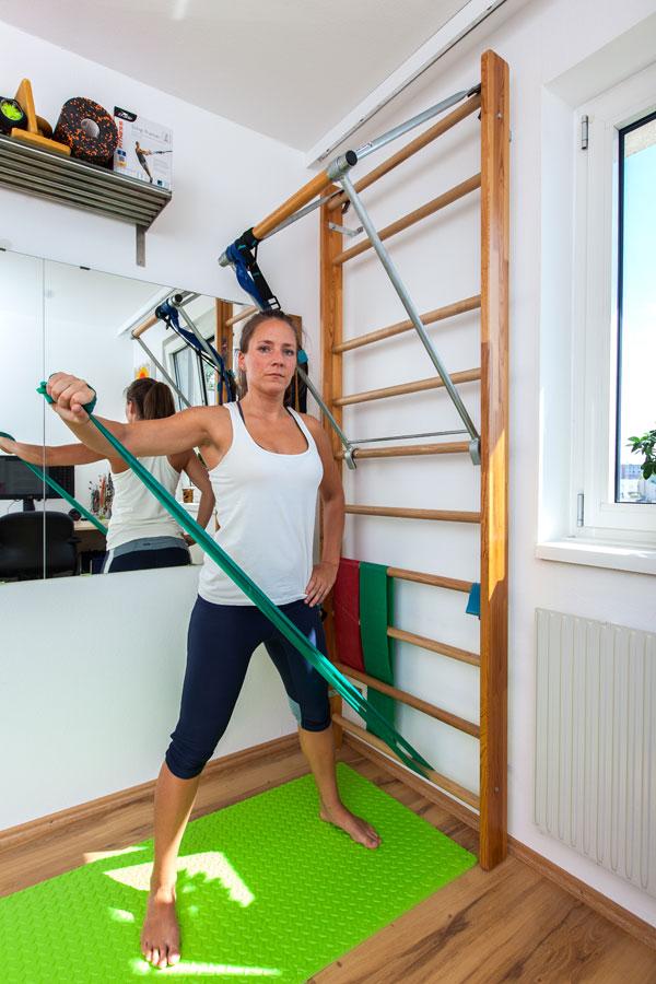 Trainerin Bernadette Hörner zeigt, wie man mit Theraband und Sprossenwand den Schultermuskel trainiert