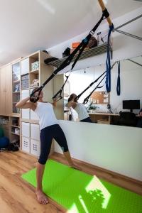 Fitnesstrainerin Bernadette Hörner demonstriert Ruderbewegung mit Suspension-Trainer von Hofer-Aldi
