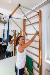 Fitnesstrainerin Bernadette Hörner demonstriert die Adjustierung der Klimmzugstange von Sport Thieme