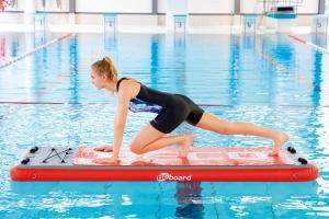 """Frau macht auf schwimmendem Brett der Firma Beco die Übung """"Mountainclimbers"""""""