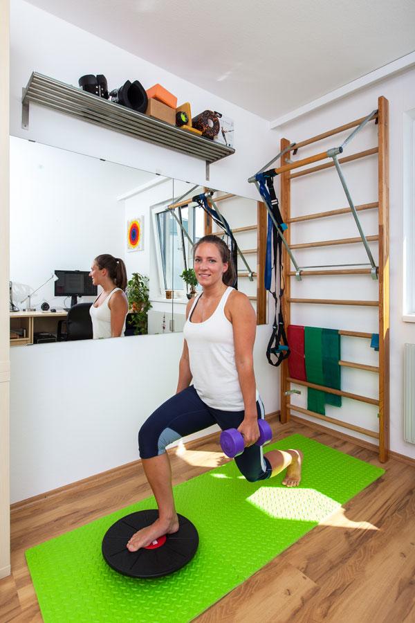Fitnesscoach Bernadette Hörner demonstriert Ausfallschritt auf Balance-Board mit Hanteln