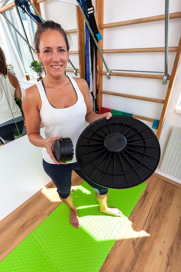 Fitnesscoach Bernadette Hörner zeigt ein Balance-Board inklusive Aufsatz für stärkeres Wackeln