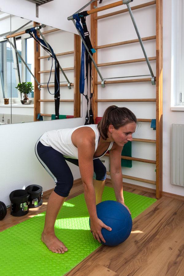Fitnesstrainerin Bernadette Hörner zeigt eine Übung für den Rückenstrecker mit Medizinball