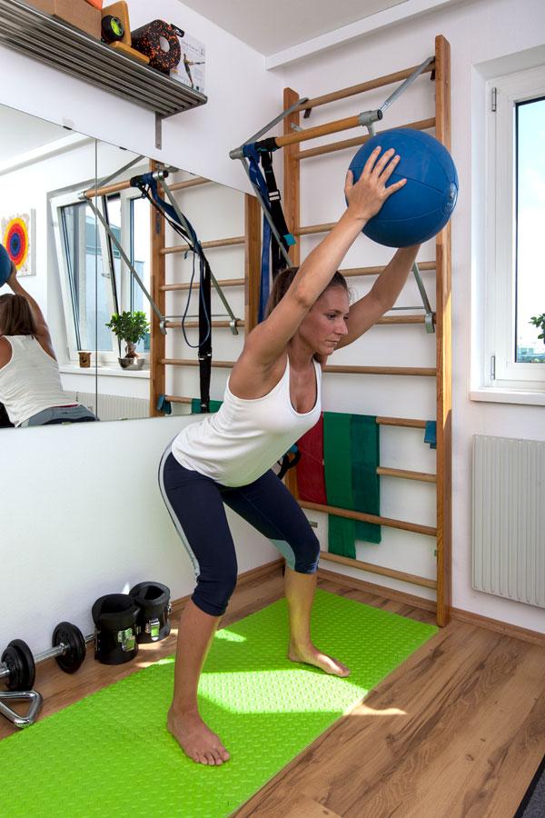 Fitnesstrainerin Bernadette Hörner zeigt eine Rückenübung mit Medizinball in ihrem Homegym
