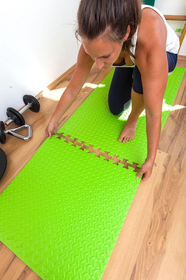 Fitnesstrainerin Bernadette Hörner demonstriert das Zusammensetzen von Fitness-Puzzlematten