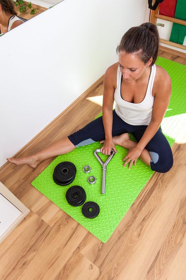 Fitness-Instructor Bernadette Hörner demonstriert eine Kettlebellstange inklusive Gewichtscheiben zum aufschrauben