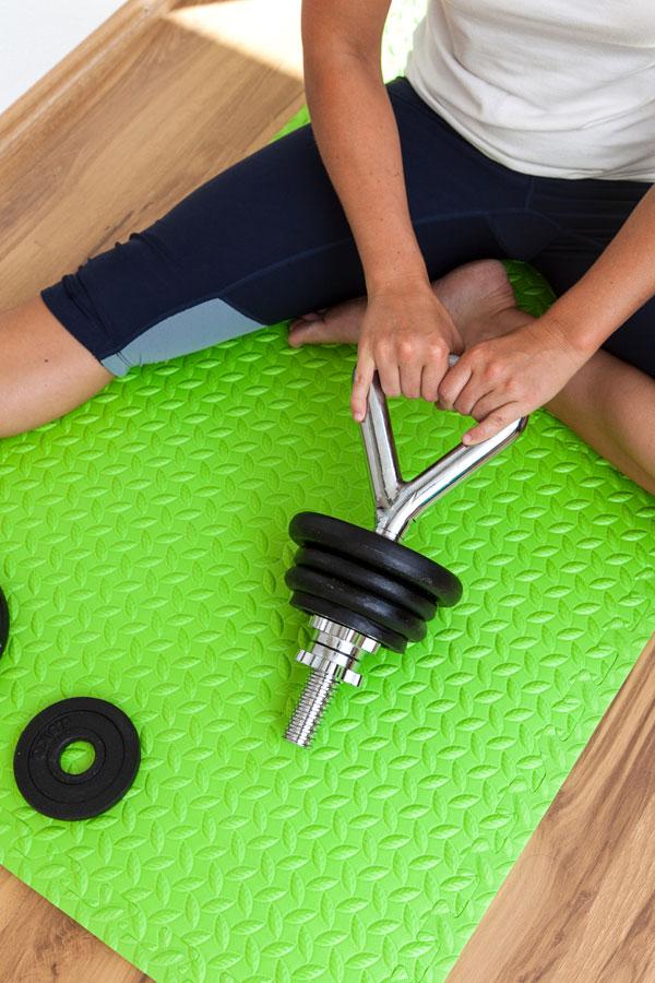 Fitness-Instructor Bernadette Hörner zeigt, wie man Hantelscheiben auf die Kettlebell-Stange schraubt