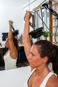 "Fitness-Instructor Bernadette Hörner demonstriert die Übung ""Press"" mit Kettlebell-Hantelstange"