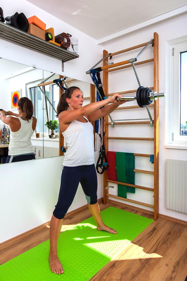 "Fitness-Instructor Bernadette Hörner zeigt die Übung ""Swing"" mit der Kettlebell-Hantelstange"