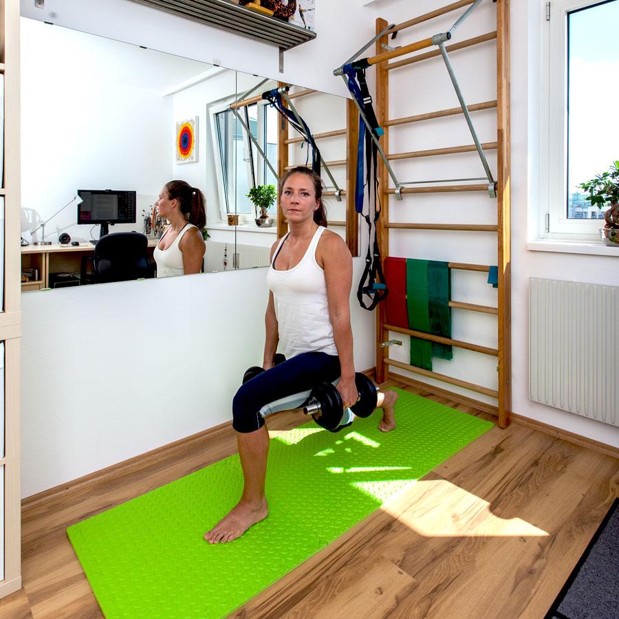 Fitnesstrainerin Bernadette Hörner demonstriert Ausfallschritt mit Kurzhanteln