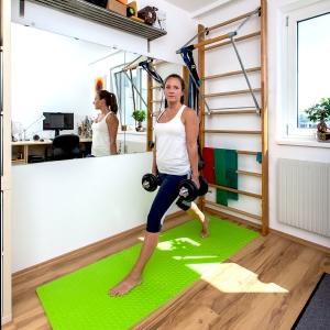 Fitnesstrainerin Bernadette Hörner zeigt eine Kniebeuge mit Kurzhanteln