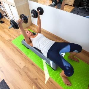 Fitnesstrainerin Bernadette Hörner demonstriert Bankdrücken mit Step und Kurzhanteln
