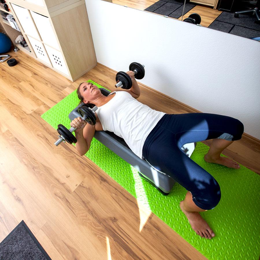Fitnesstrainerin Bernadette Hörner demonstriert die Übung Bankdrücken mit Kurzhanteln auf Step liegend