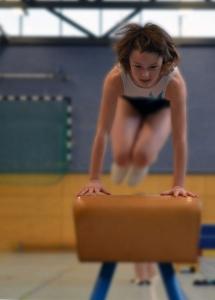 Kind springt Hocke über Turnbock
