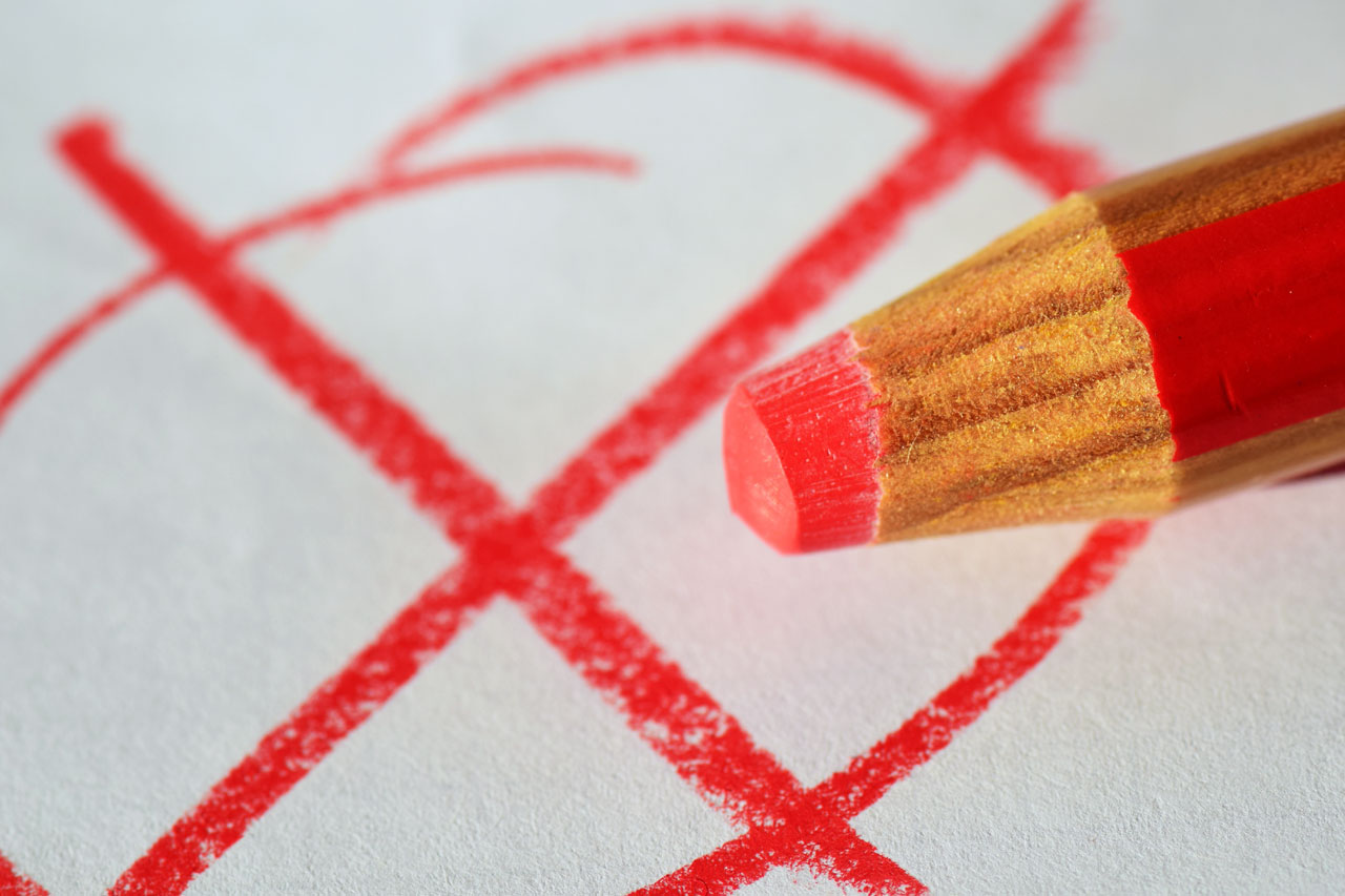 Stift malt rotes Wahlkreuz auf Papier
