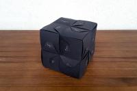 Adventkalender in Form eines schwarzen Würfesl mit binären Zahlencodes