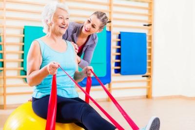 Ältere Dame trainiert mit Theraband