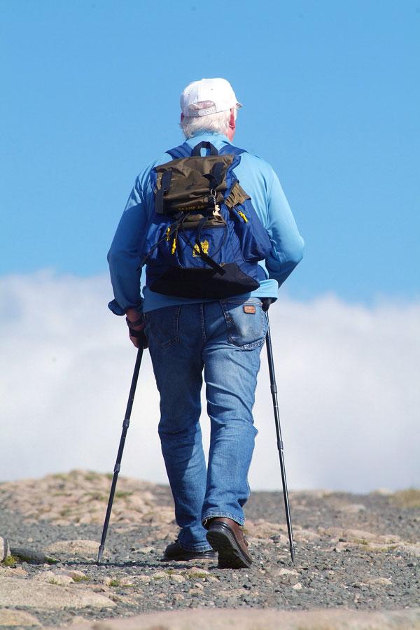 Rentner marschiert mit Nordic-Walking-Stöcken