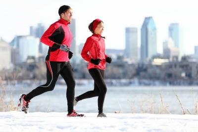 Frau und Mann joggen bei Schnee in einer Großstadt