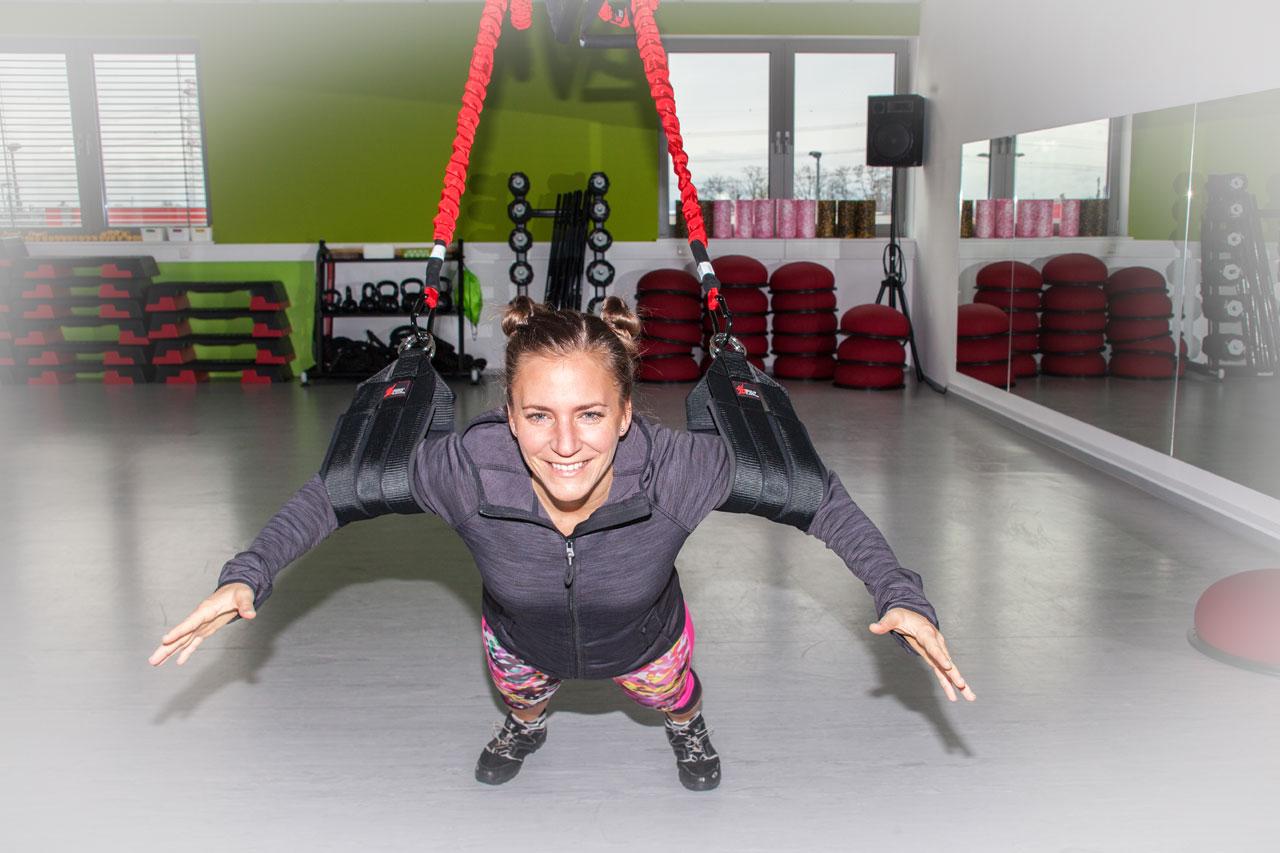Fitnessbloggerin Bernadette Hörner bei einer Brustmuskel-Übung mit dem 4D Pro Bungee-Fitness-Schlingentrainer. Ort: Bodyzone Deutsch Wagram bei Wien.