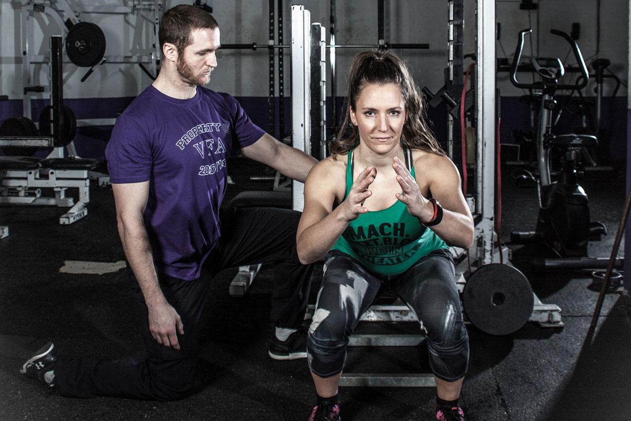"""Vienna Vikings-Coach Christoph Putz korrigiert die Gelenksstellung von Fitnessbloggerin Bernadette Hörner während der Übung """"tiefe Hocke"""""""
