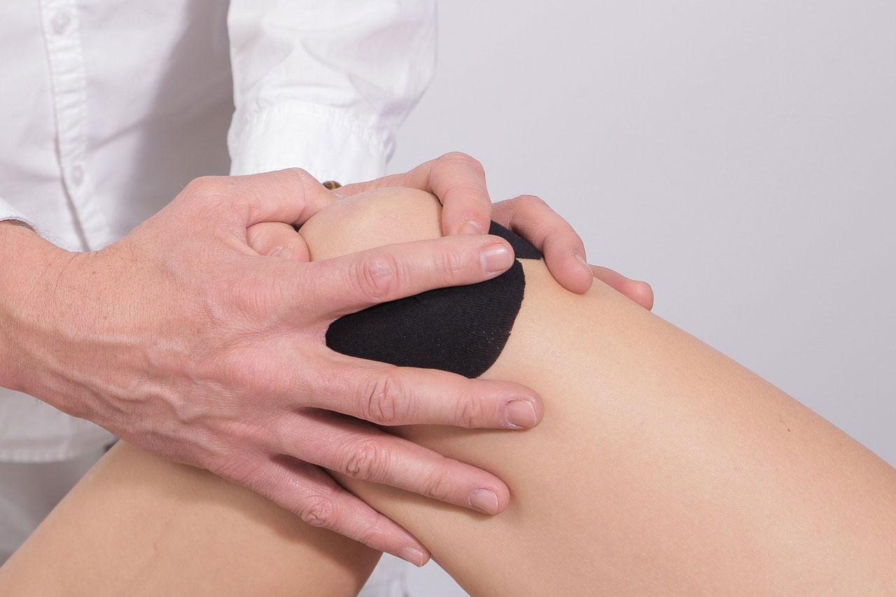 Arzt untersucht Knie einer Patientin