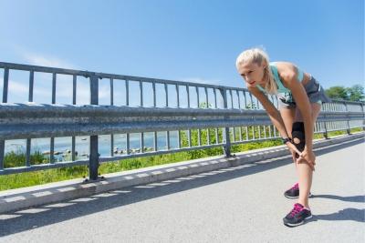 Läuferin pausiert Joggingrunde aufgrund von Knieschmerzen