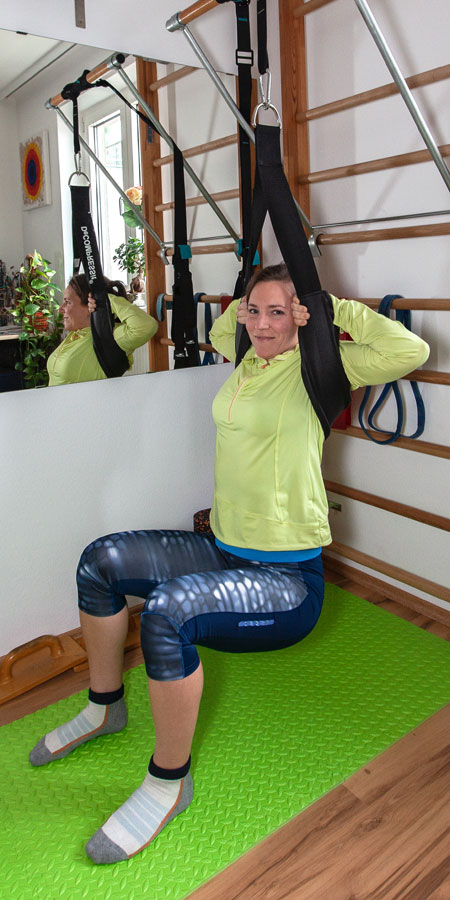 Fitnessbloggerin Bernadette Hörner zeigt die Squat-Position mit dem Decompressit-Rückengurt