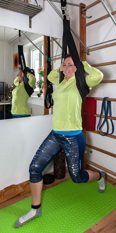 Fitnessbloggerin Bernadette Hörner zeigt einen Ausfallschritt mit dem Decompressit-Trainingsgerät