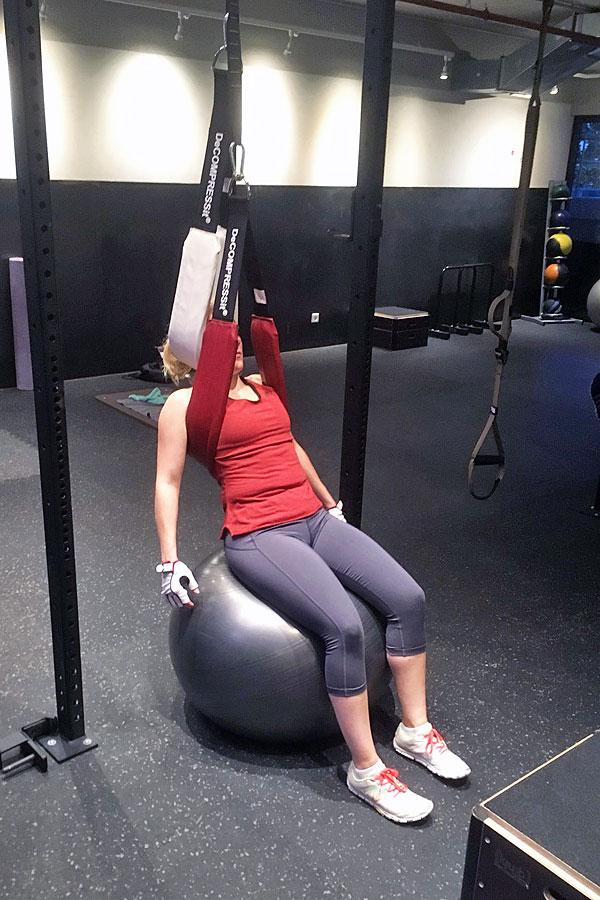 Eine Decompressit-Kundin demonstriert, wie der Nacken-Gurt und ein Sitzball in das Training integriert werden können