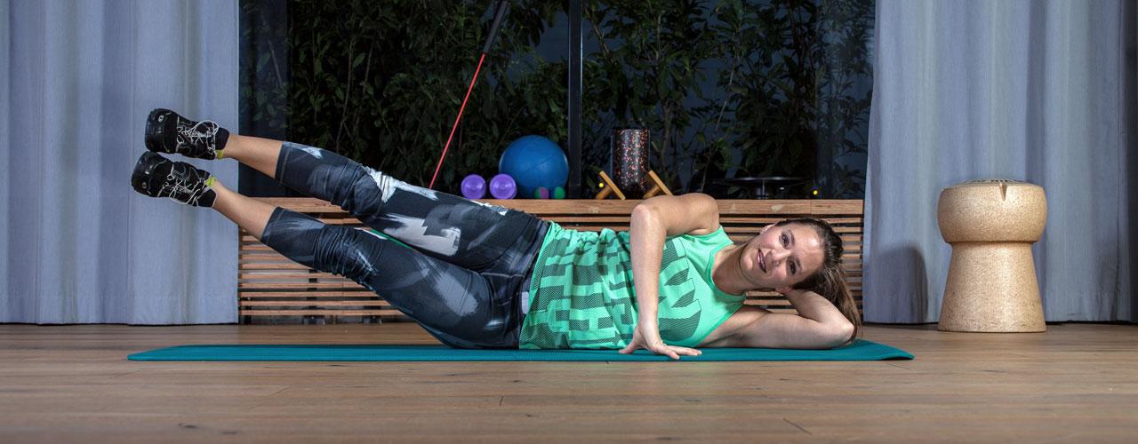 """Fitnesstrainerin Bernadette Hörner demonstriert eine Übung """"Beine heben in Seitlage"""" für die seitlichen Bauchmuskeln"""
