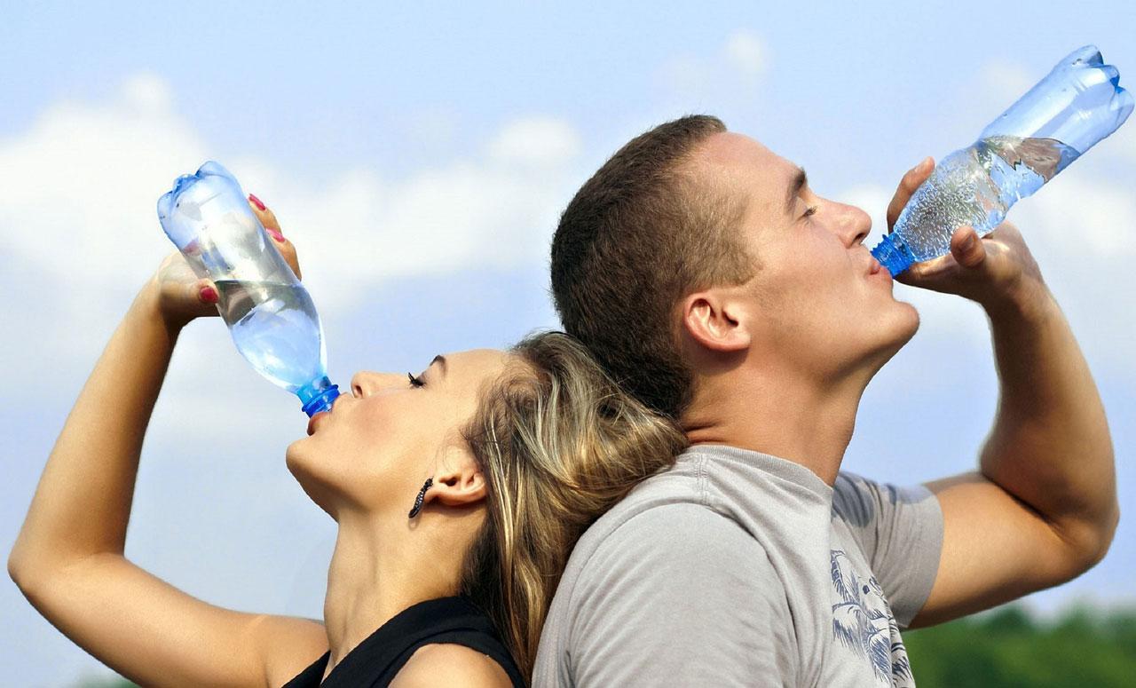Mann und Frau trinken aus Wasserflasche