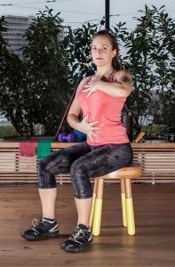 Personal Trainerin Bernadette Hörner demonstriert eine Übung zur korrekten Sitzhaltung