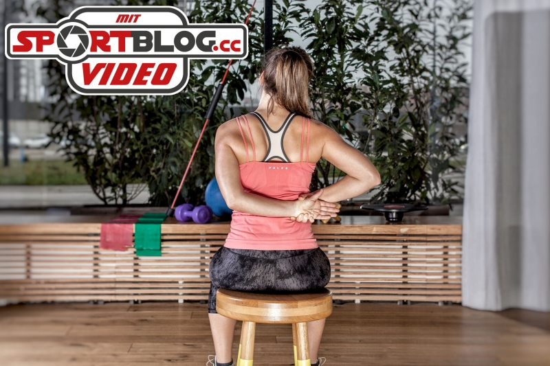 Personal Trainerin Bernadette Hörner zeigt eine Dehnung für den Nacken im Sitzen