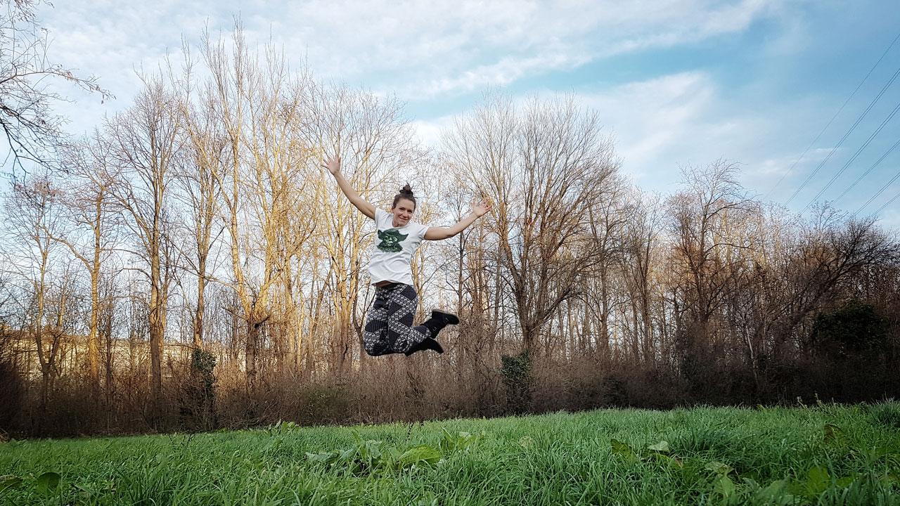 Fitnessbloggerin Bernadette Hörner springt im T-Shirt im Winter auf einer Wiese (Erholungsgebiet Wien Simmering)