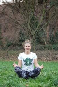 Fitness Trainerin Bernadette Hörner beim winterlichen Outdoor-Yoga im Schneidersitz