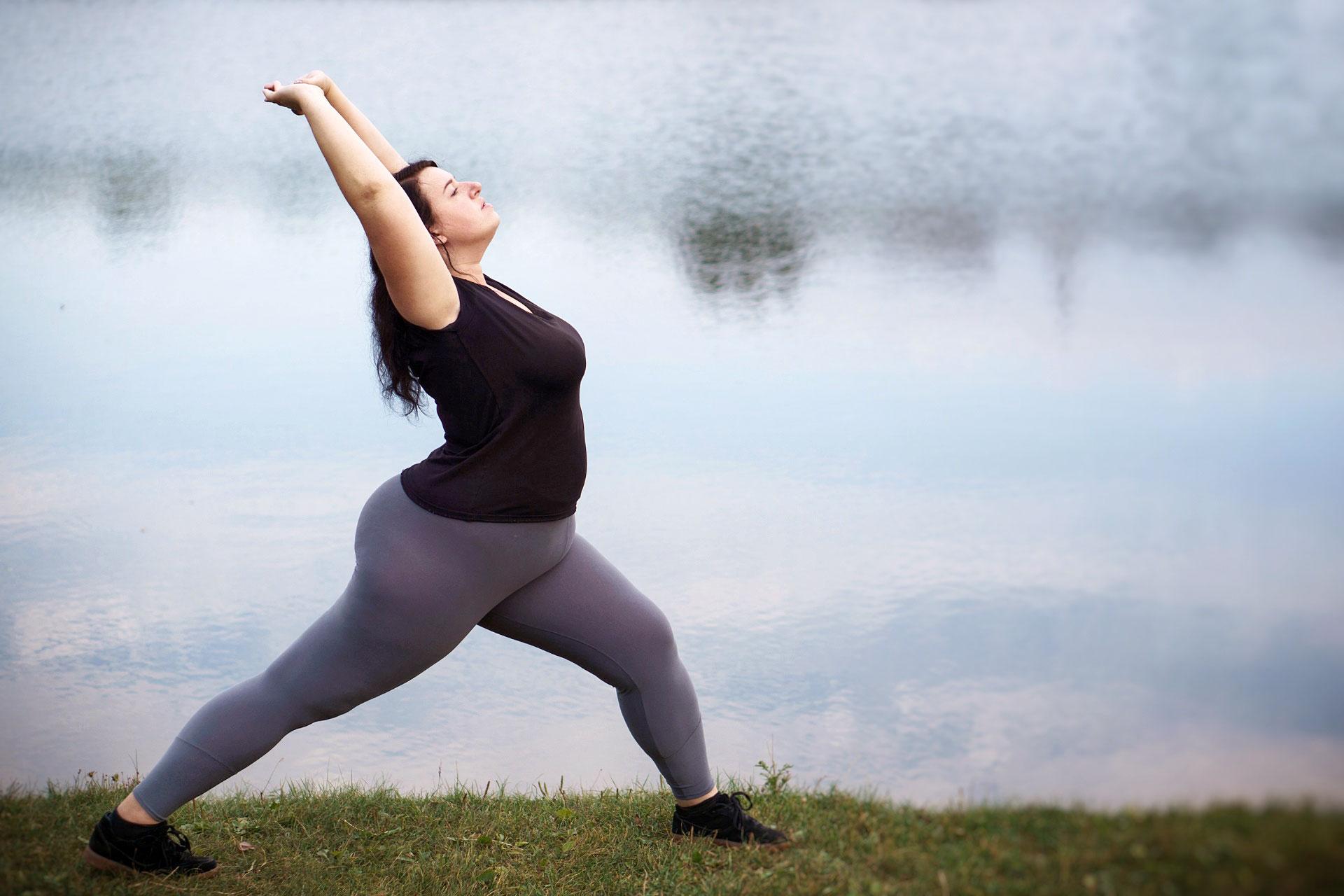 Frau mit erhöhtem Körperfettanteil beim Yoga