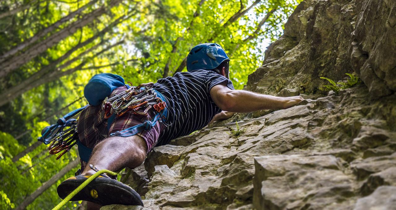Mann beim Sportklettern auf Felswand
